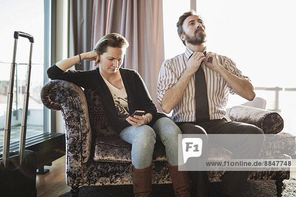 Geschäftspaar entspannt auf Chaiselongue im Hotelzimmer