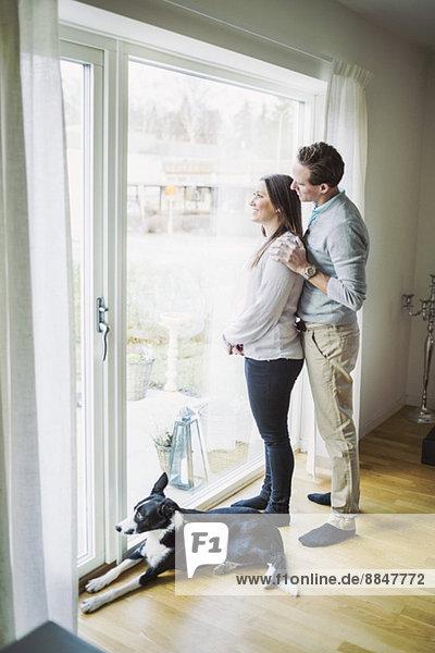 Seitenansicht des Paares beim Blick durchs Fenster zu Hause