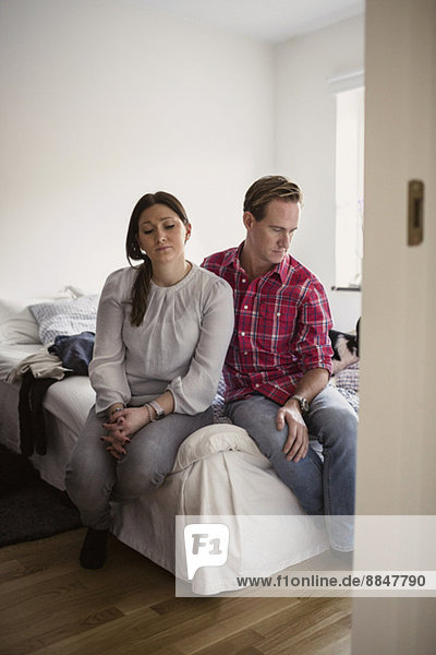 Trauriges Paar zu Hause auf dem Bett sitzend