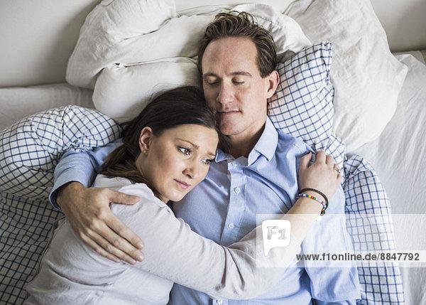Hochwinkelansicht einer traurigen Frau  die den Mann umarmt  während sie im Bett liegt.