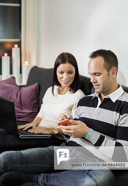 Paar mit Handy und Laptop auf dem Sofa zu Hause