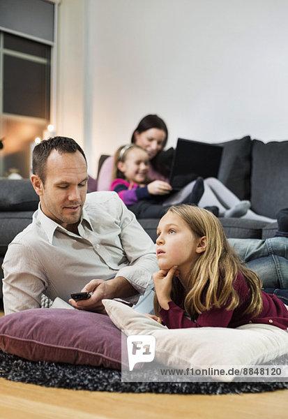 Vater und Tochter beim Fernsehen am Boden mit Familie im Hintergrund