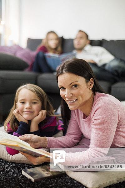 Porträt der glücklichen Mutter und Tochter mit Geschichtenbuch im Wohnzimmer