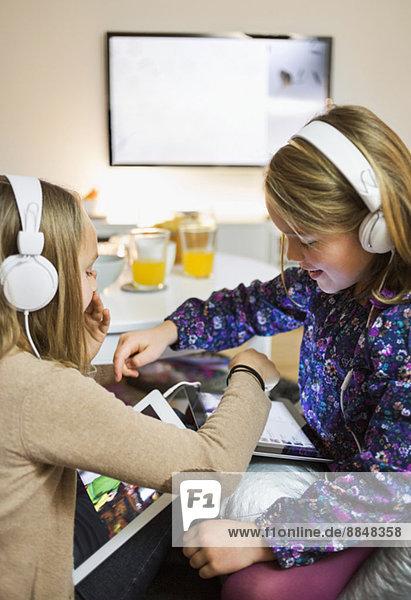 Schwestern beim Musikhören auf digitalen Tabletts im Wohnzimmer
