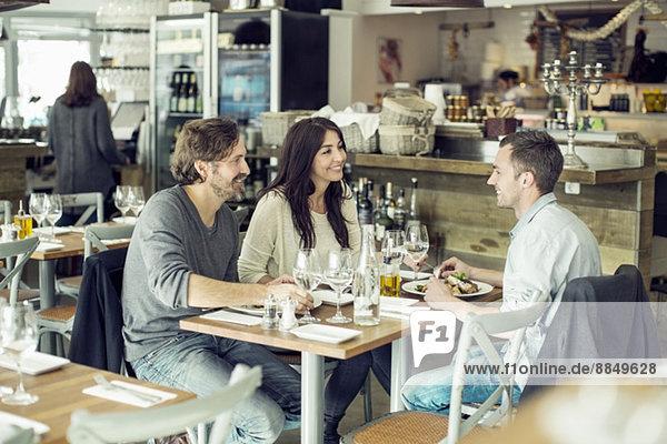 Glückliche Freunde diskutieren bei Tisch im Restaurant