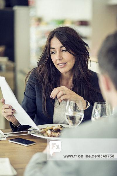 Geschäftsfrau im Gespräch mit männlichem Kollegen am Restauranttisch