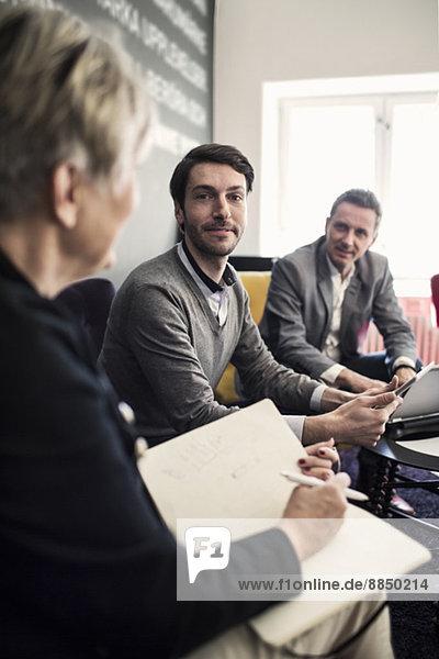 Porträt eines selbstbewussten Geschäftsmannes mit Kollegen in der Lobby