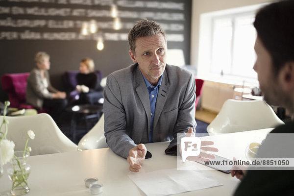 Geschäftsmann gestikuliert im Gespräch mit männlichen Kollegen am Schreibtisch