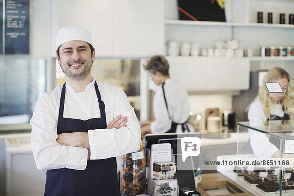 Porträt eines selbstbewussten Besitzers  der im Cafe die Arme verschränkt hält