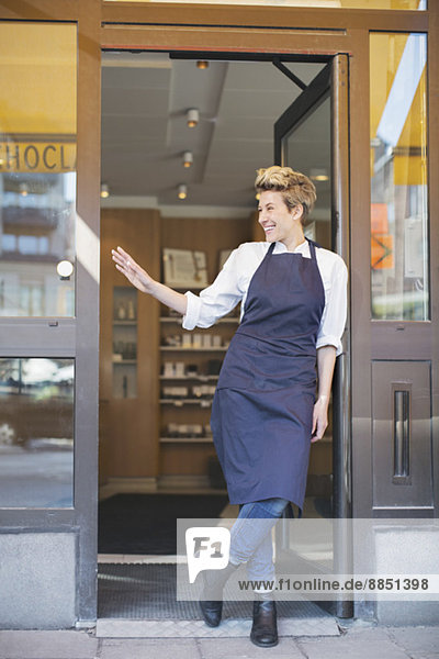 Volle Länge der glücklichen Besitzerin beim Stehen am Café-Eingang