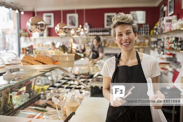 Porträt der glücklichen Verkäuferin beim Käseschneiden an der Theke im Supermarkt