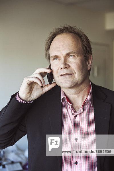 Erwachsener Mann mit Handy zu Hause