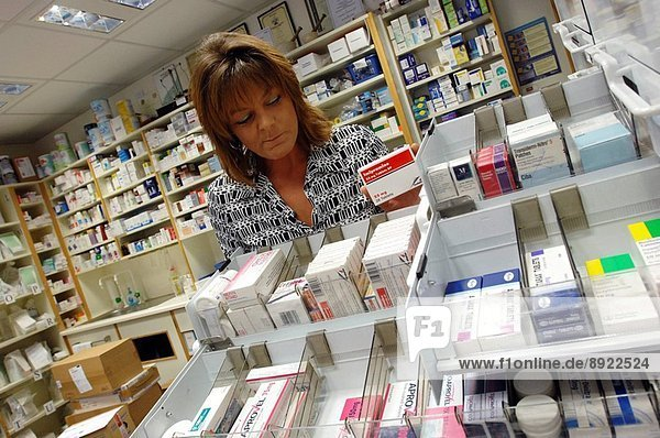 A female pharmacist keeping tidy the medicine drawers in a dispensary.
