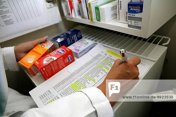 A pharmacist stock checks various drugs and medication.