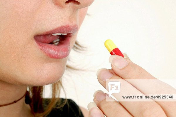 Drugs capsule on the tongue of a young woman.
