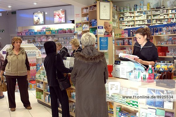 A customer at the counter of a retail chemist being served by a pharmacist in front of the dispensary