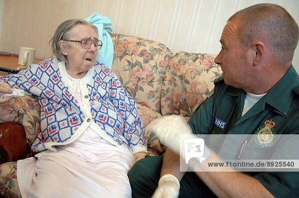 A paramedic from the NHS London Ambulance Service caring for an elderly woman.