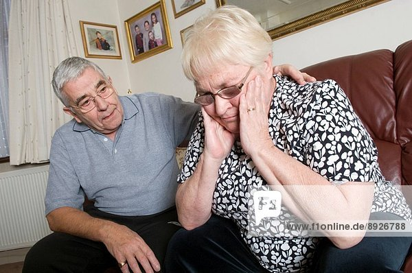 A worried elderly couple discuss a family problem