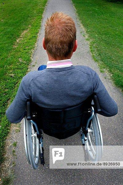 A man wheelchair bound  wheeling through a park.