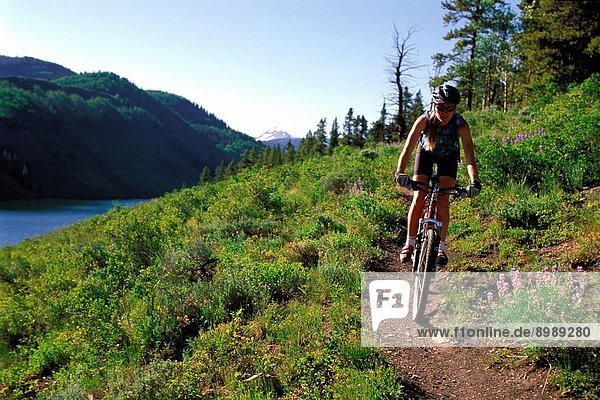 Colorado. Woman Mountain Biking Along Lake Long
