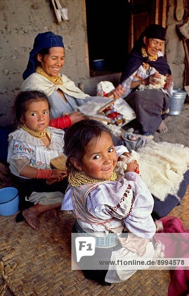 OTAVALO INDIAN WOMAN with FAMILY CARDING WOOL in the MARKETPLACE _ OTAVALO  ECUADOR
