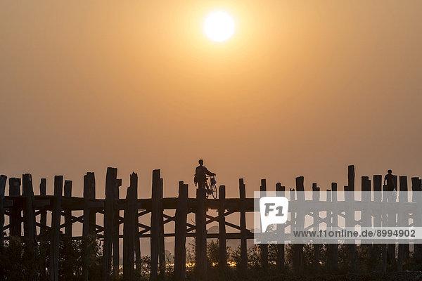 Man riding a bike on a teak bridge  U Bein Bridge across Thaungthaman Lake at sunset  Amarapura  Mandalay Division  Myanmar