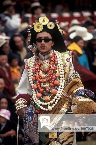 Female Khampa wears gold hair pieces & gau boxes  zee stones & coral at the Litang Horse Festival _ Sichuan Province  China
