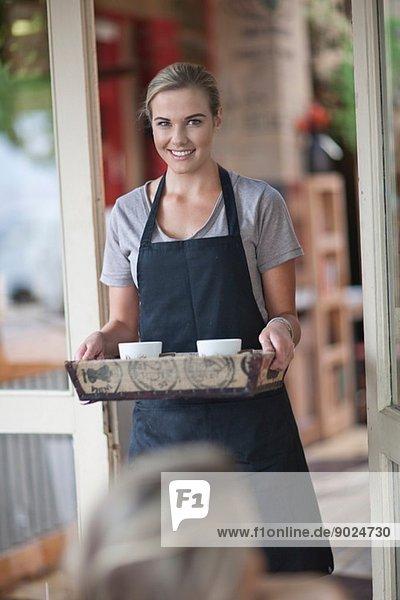 Junge Kellnerin mit einem Tablett mit Kaffeetassen im Café