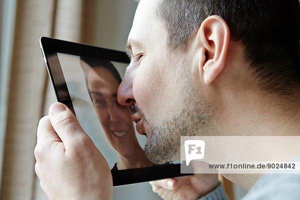 Mittlerer Erwachsener Mann  der den Bildschirm eines digitalen Tabletts küsst