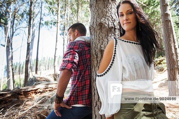 Junges Paar  das sich im Wald an einen Baum lehnt