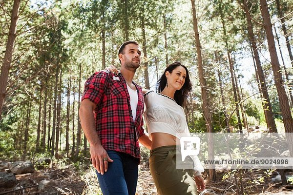 Junges Paar geht durch den Wald  Arm um Arm.
