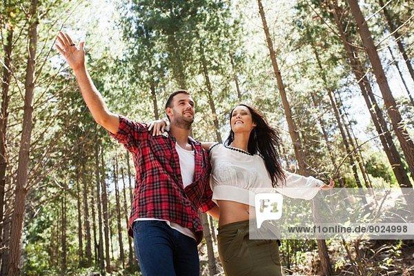 Junges Paar  das im Wald herumalbert  Arme ausgestreckt