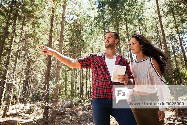 Junges Ehepaar im Wald  Mann zeigt auf