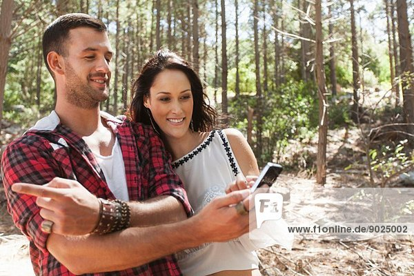 Young couple in forest  man pointing