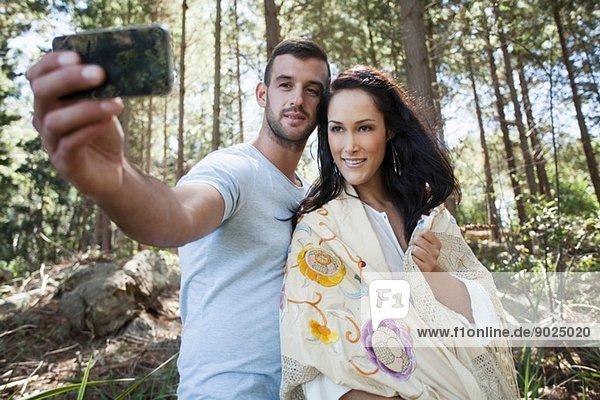 Junges Paar beim Selbstporträtfotografieren im Wald