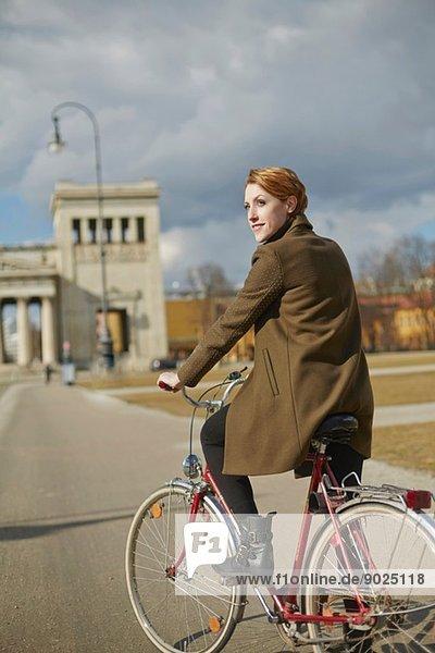 Radfahrende Frau  Denkmal im Hintergrund  München  Deutschland