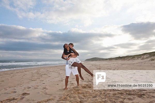 Junges Paar  das am Strand herumalbert.