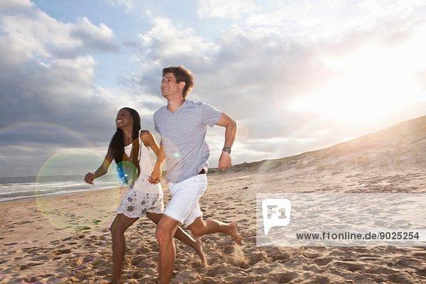 Junges Paar  das am Strand läuft