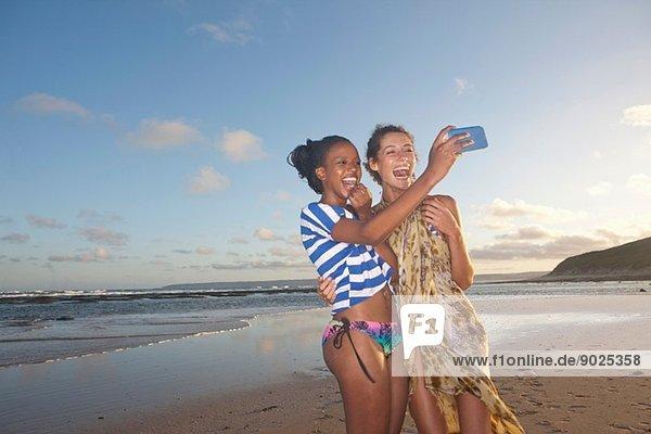 Freunde am Strand beim Selbstporträtfotografieren