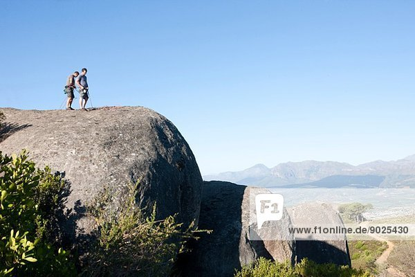 Junge männliche Kletterer  die Seile und Gurte am Fels befestigen
