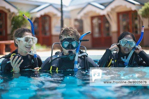 Drei junge erwachsene Taucher trainieren im Schwimmbad