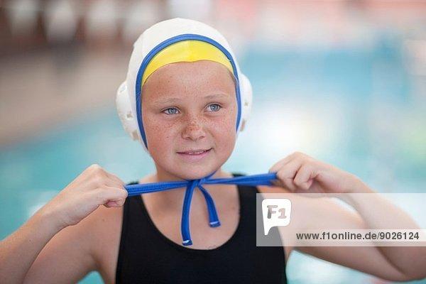 Porträt Schulmädchen Wasserballspielerin beim Befestigen der Badekappe