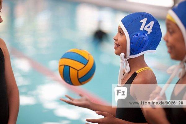 Schulmädchen Wasserballerinnen am Pool mit Ball