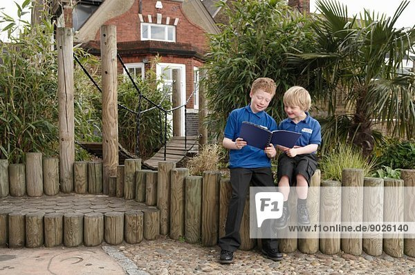 Zwei Schuljungen beim Lesen des Buches am Blockzaun