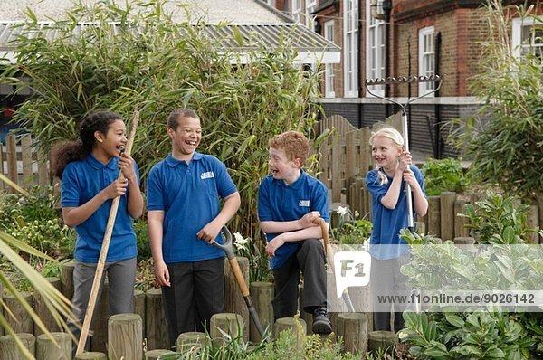 Gruppe von vier Schülern mit Gartengeräten