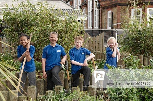 Porträt von vier Schulkindern mit Gartengeräten