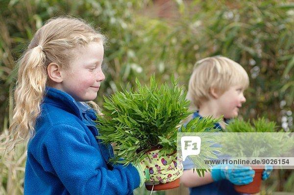 Schuljunge und Mädchen mit Pflanzen im Garten