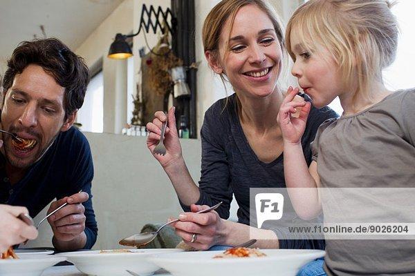 Mittlere erwachsene Eltern und zwei Töchter  die eine Spaghetti-Mahlzeit essen.