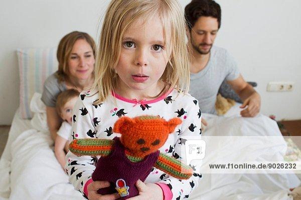 Porträt eines mürrischen jungen Mädchens auf dem Bett ihrer Eltern
