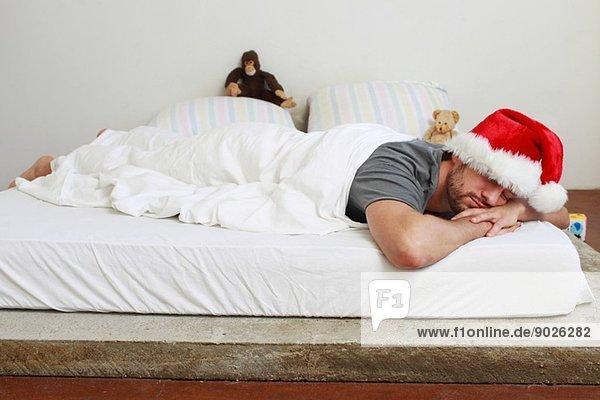 Mittlerer erwachsener Mann mit Weihnachtsmann im Bett schlafend